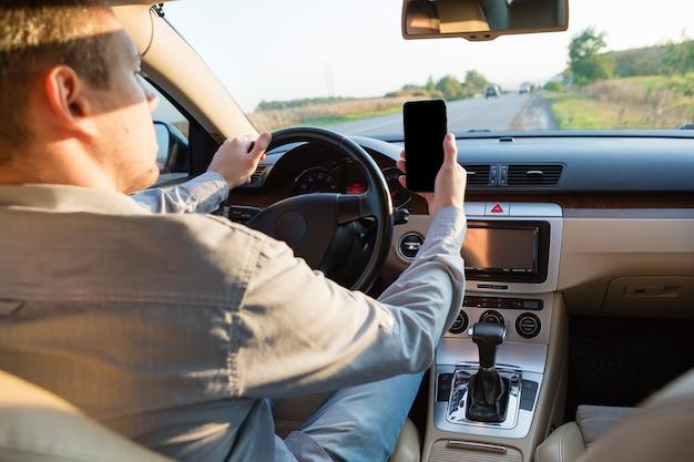 Hand unter verwendung des telefons, das einen text beim fahren zur arbeit sendet