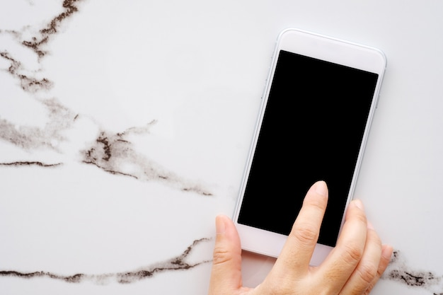 Hand unter verwendung des weißen intelligenten telefons mit leerem bildschirm auf weißem marmortabellenhintergrund