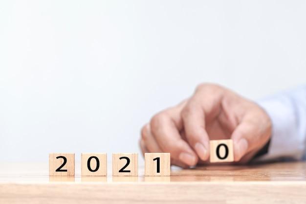 Hand verändert einen holzwürfel symbolisch von 2020 bis 2021