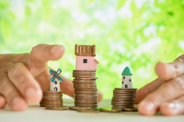 Hand verwöhnte münzen und modell des kleinen hauses
