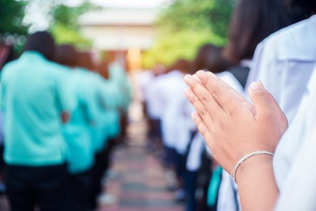 Hand von asiatischen studenten zollen dem buddha respekt