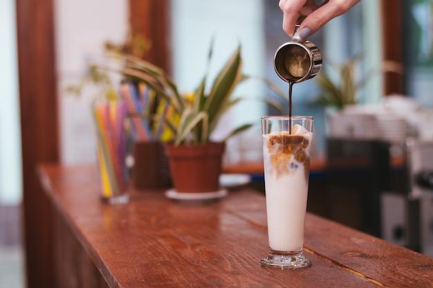 Hand von barista auslaufende milch des latte- oder cappuccinokaffees machend