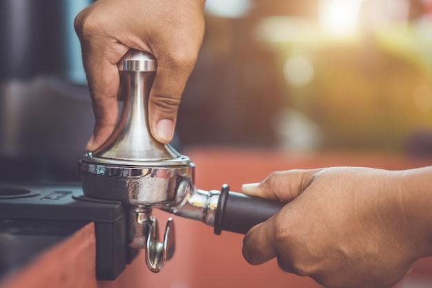 Hand von barista kaffeestampfer halten und kaffeezubereitung machen