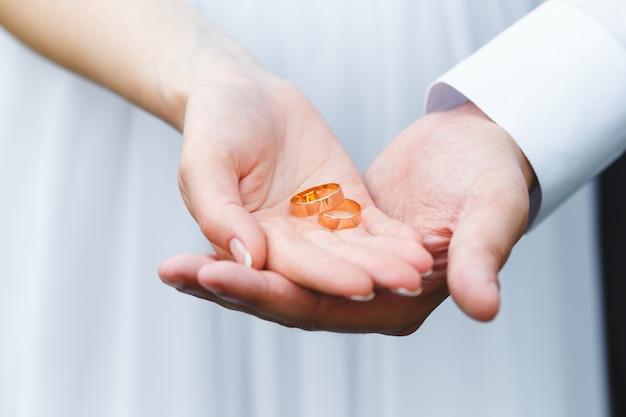 Hand von braut und bräutigam mit eheringen auf den handflächen