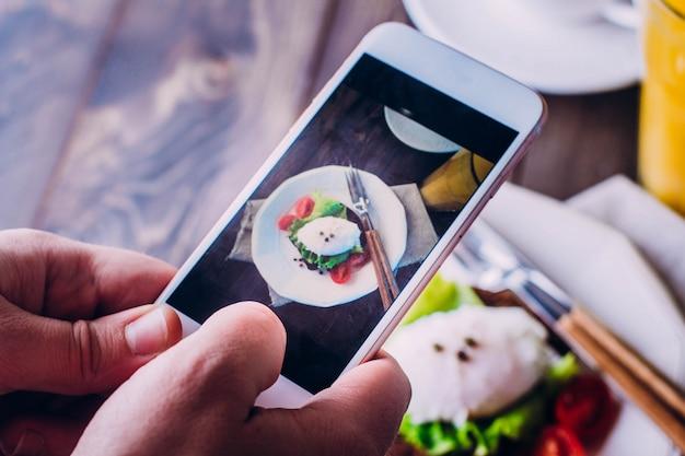 Hand von den männern, die bildfotolebensmittel mit mobilem smartphone nehmen