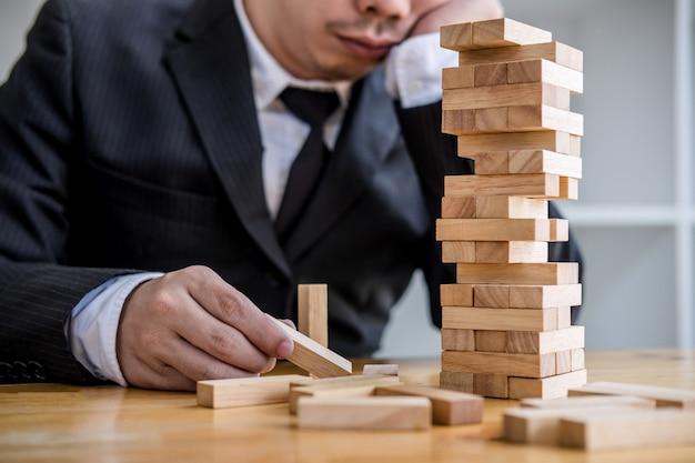 Hand von den wirtschaftlern, die hölzernen block auf den turm, konzept des alternativen risikos setzen und ziehen