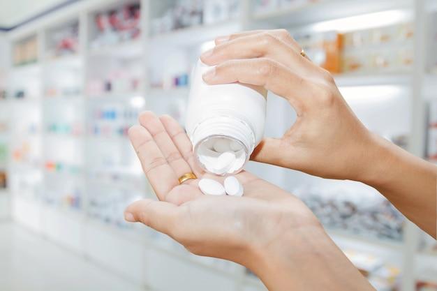 Hand von doktor medizinflasche auf medizinschrank und speichermedizin und apothekendrogerie halten