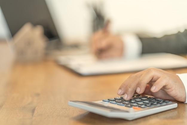 Hand von geschäftsleuten, die zinsen, steuern und gewinne berechnen, um in immobilien und hauskäufe zu investieren