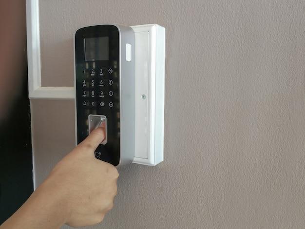 Hand von menschen und elektronischer digitaler tür, fingerabdruckscan zum entsperren des türsicherheitssystems