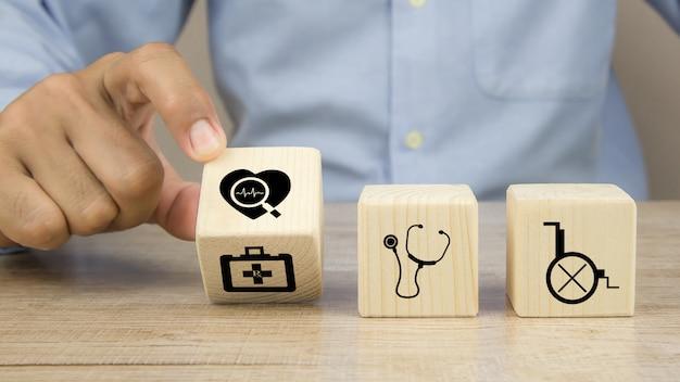Hand wählen herzsymbol herzrhythmus oder puls auf würfel holzspielzeugblöcke stapeln sich mit anderen medizinischen symbolen.