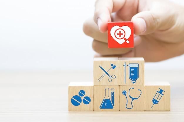 Hand wählen holzblock mit symbol für medizin und gesundheit.