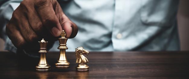 Hand wählen könig schachstand teamwork auf schachbrett.