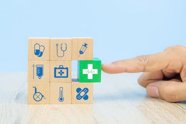 Hand wählen medizinische ikone auf würfel holzspielzeugblöcke stapeln sich mit anderen medizinischen symbolen.