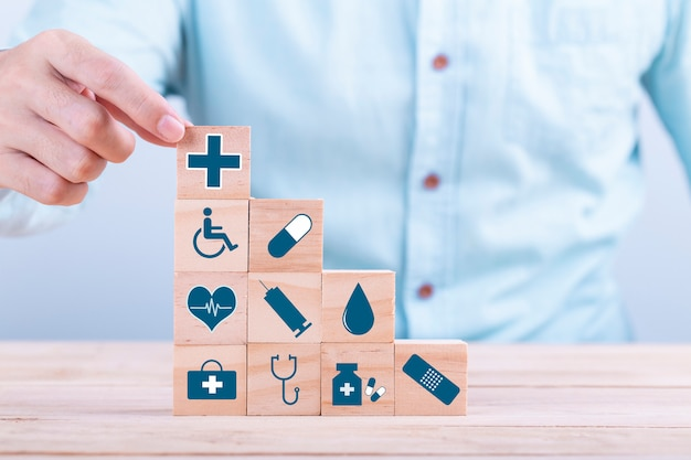 Hand wählt ein medizinisches symbol des emoticonikonen-gesundheitswesens auf holzklotz-, gesundheitswesen- und krankenversicherungskonzept