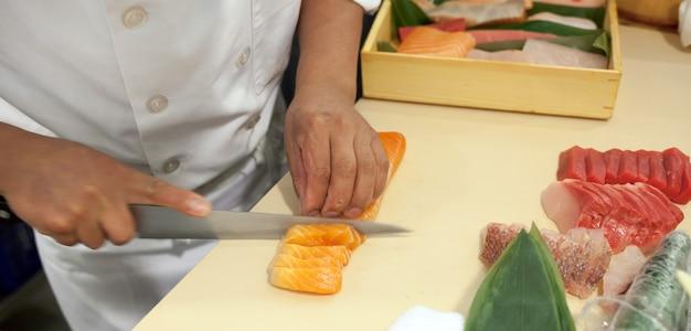 Hand war geschnittener fisch, um sushi zu machen