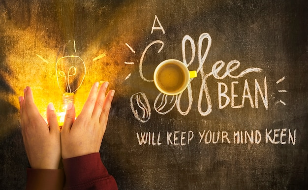 Hand, welche die belichtete glühlampe mit mitteilung auf tafel bedeckt