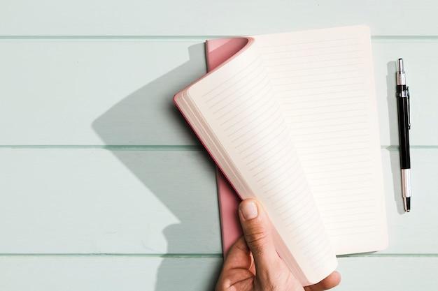 Hand, welche die notizbuchseiten mit rosa abdeckungen dreht