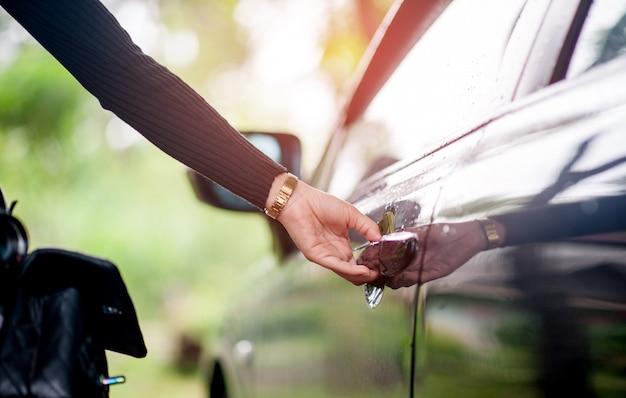 Hand, welche die schwarze autotür öffnet