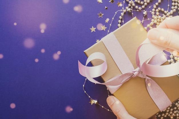 Hand wickeln goldene geschenkbox mit glitzerrosa band festlichen feiertagen weihnachten neujahrshintergrund