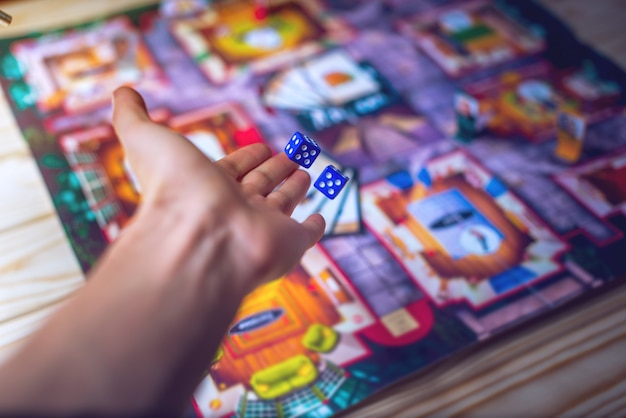 Hand wirft die würfel auf das brettspiel
