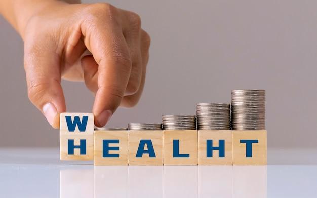 Hand wirft einen holzwürfel mit den worten reichtum für gesundheit und einem wachsenden haufen münzen