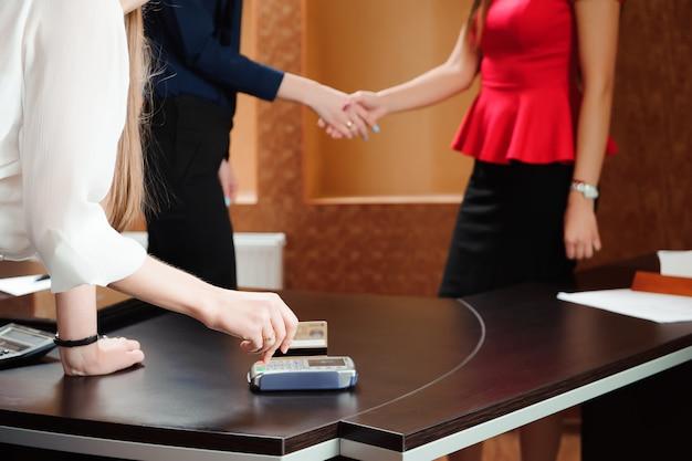 Hand wischen debitkarte auf pos terminal, leute im büro halten eine konferenz und diskutieren strategien.