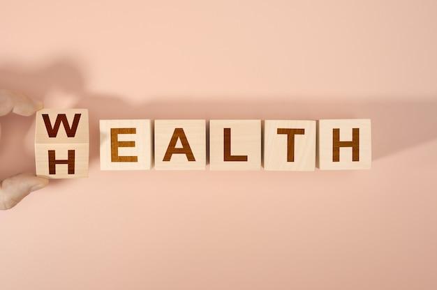 Hand würfelt und ändert das wort gesundheit in reichtum. konzept der wahl der priorität in leben und lebensstil.