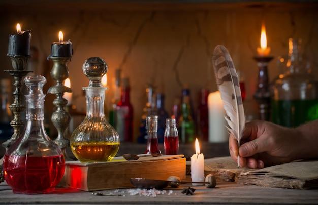 Hand, zaubertrank, alte bücher und kerzen