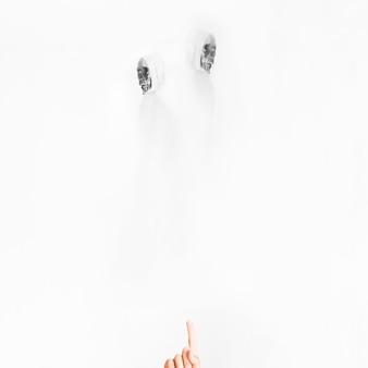 Hand zeigt auf engel des todes in weißen kostümen