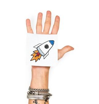 Hand zeigt eine haftnotiz mit einem raketenstart