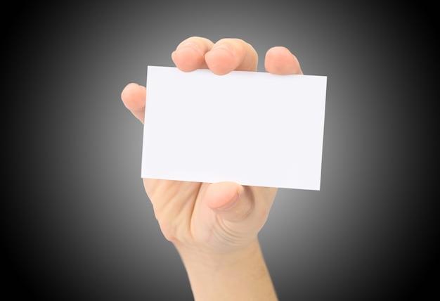 Hand zeigt leere visitenkarte. auf einem schwarzen hintergrund.