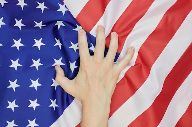 Hand zerknitterte amerikanische nationalflagge der usa. revolutionäres politisches wahrheitskonzept. wirtschaftsembargos sanktionen oder unabhängigkeitstag symbol.