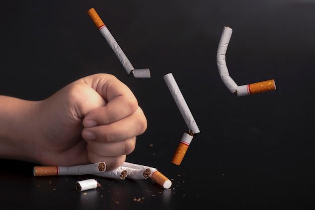 Hand zertrümmerte zigaretten hören auf, konzept zu rauchen