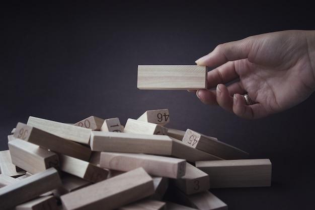 Hand zieht einen holzblock aus einem stapel der gleichen blöcke heraus. personalwesen, management, rekrutierung. plan und strategie im geschäft. risikokonzept. Premium Fotos