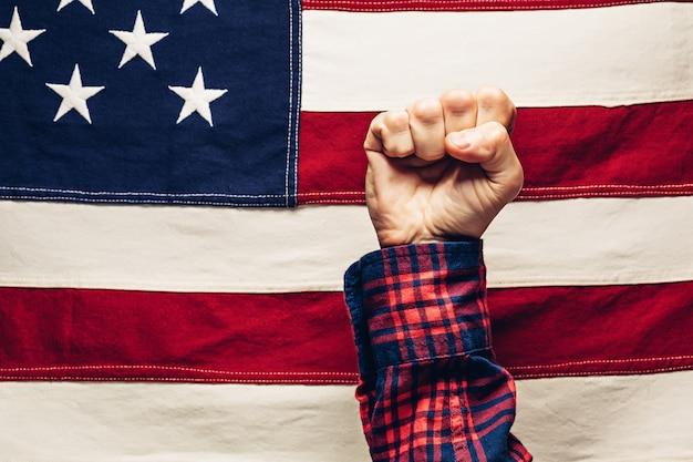 Hand zur faust geballt gegen uns flagge. stärke, leistung und zuverlässigkeit des usa- und labor day-konzepts