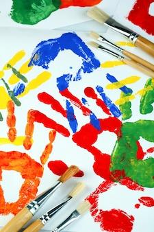 Handabdrücke von farbe und pinseln auf weißer oberfläche