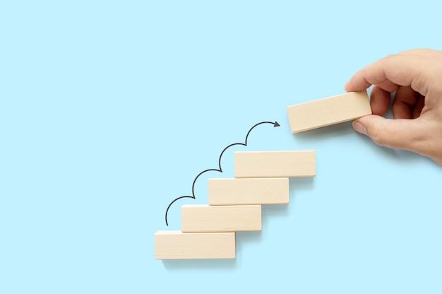 Handanordnung holzblockstapelung als stufentreppe mit pfeil nach oben