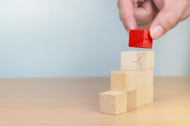 Handanordnung von holzblockstapeln als stufentreppe. leiter karriereweg konzept für den erfolgsprozess des unternehmenswachstums