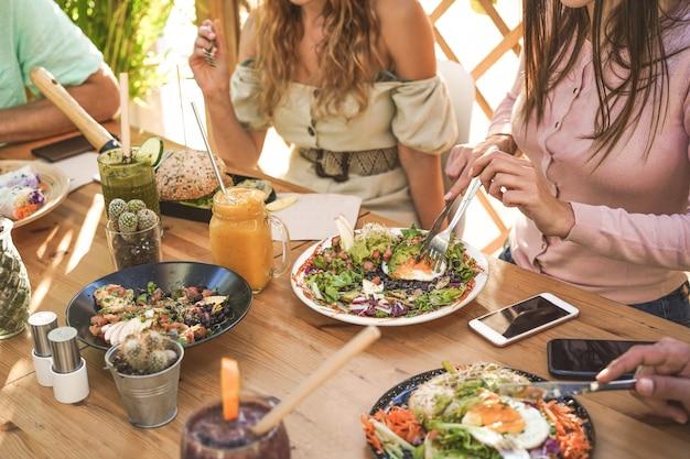 Handansicht der jungen leute, die brunch essen und smoothies schüssel mit ökologischen strohhalmen im trendigen bar-restaurant trinken