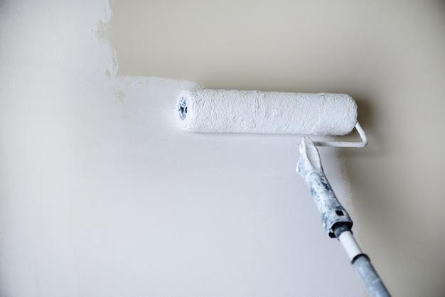 Handanstrichwand mit farbrolle, pastellfarbe. wohnungsrenovierung, reparatur, gebäude- und wohnkonzept. platz kopieren. werkzeuge zum malen von wänden.