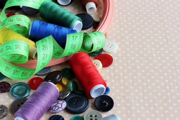 Handarbeiten und nähen: verschiedene knöpfe, farbige fäden, reifen und klebeband zum messen des tisches