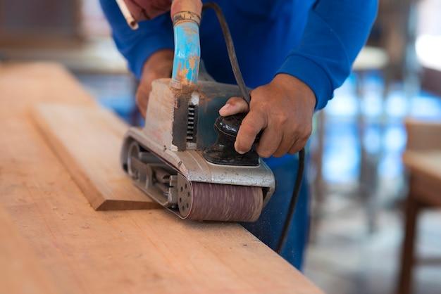 Handarbeiter schleift das holz mit einer schleifmaschine