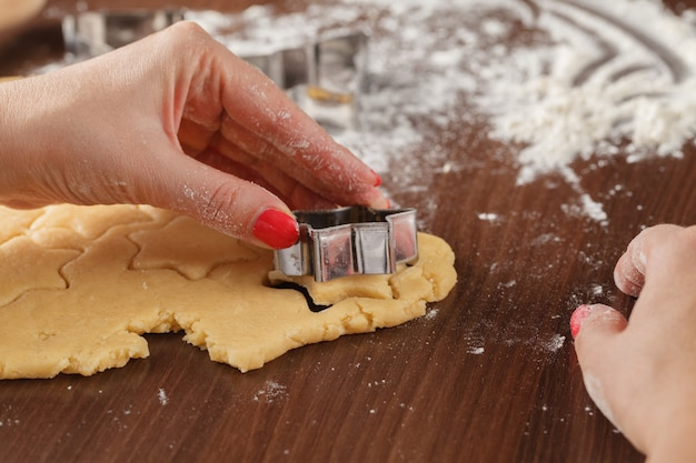 Handausschneiden von formen aus ausgerolltem ingwerplätzchenteig mit sternschneidern
