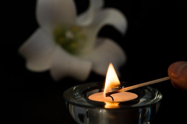 Handbeleuchtungs-teelichtkerze mit weißer lilie im hintergrund