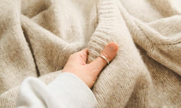 Handberührendes gestricktes wolltuch oder warmer flauschiger pullover handarbeit strickende wollstoffoberfläche