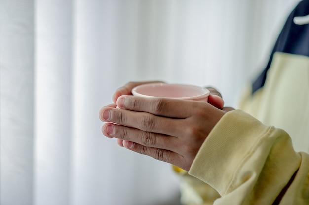 Handbild und kaffeetasse trinkendes konzept des kaffees