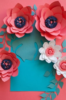 Handcraft kreativen dekorativen blumenrahmen gemacht von den papierblumen und von den blättern, karte für einladung mit verschiedenen blättern auf einem blau. flache lage.