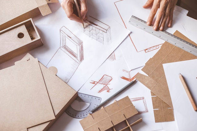 Handdesigner zeichnet eine skizze der papierverpackung.