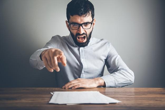 Handdokument des wütenden mannes auf schreibtisch