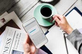 Hände, die das Herunterladen des Handys mit Kaffeetasse-Getränk halten